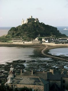 "St Michael's Mount is a tidal isle located 400 yards off the Mount's Bay coast of Cornwall. A civil parish & united w/ the town of Marazion by a man-made causeway of granite setts,passable between mid-tide & low water.Its Cornish language name — literally, ""the grey rock in the wood"" may represent a folk memory of a time before Mount's Bay was flooded.Remains of trees have been seen at low tides following storms  & radiocarbon dating established the submerging of the hazel wood at about 1700…"