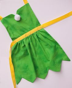 Add pixie dust and slippers and your little one can be Tinkerbell from Pixie Hollow. Dress up at its most comfortable and adorable. 5 size options allow them to fit girls ages 18m-10 years and adjustable neck and waist ties make them even more flexible in fit. XS fits 18 months S fits 2/3 years M 4/5 years L 6/7 years XL 8/9/10 These aprons are perfect for your upcoming Disneyland, Disney World, or Disney cruise events. They are light to pack and easy to change so your princess can match…