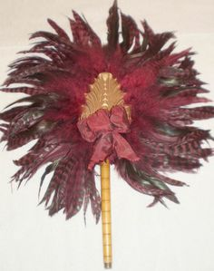 FEATHER FAN = BURGANDY COLOR FEATHERS=WOOD BOBBIN HANDLE & WOOD CENTER