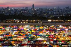 As night falls in Bangkok, Thailand, this colourful market comes alive with colour and lig...