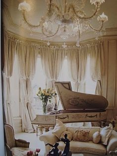 the white, chandelier, window drapes, and piano exude elegance.
