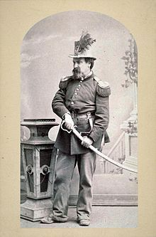 Joshua Norton in full military regalia with his hand on the hilt of a ceremonial…