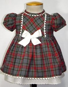 Vestido para bebe niña en villela de cuadros rojos y gris, adornado en piquillo beige y tirabordada beige en la combinación. Forrado