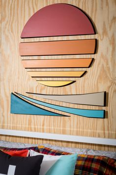 A rainbow-colored sun sets over the water in this graphic wall art. The wood grain of the wall is the perfect neutral backdrop.