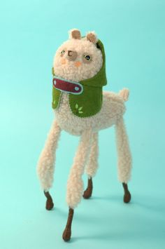 A nice woolly alpaca with an olive green hooded cape.