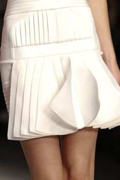 White dress with horizontal and vertical pleats and lovely layers - garment details; close up fashion // David Koma