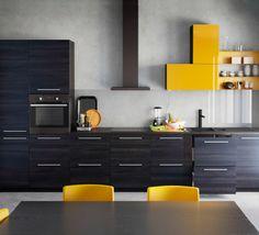 Fastmonteret IKEA køkken med skabe med sort træmønster og gul højglans.