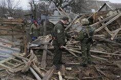 Ukrainalaisnainen tutkii kotinsa raunioita ukrainalaisten sotilaiden kanssa Sartanan kylässä Mariupolin alueella 5.2.2015