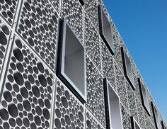 Façade en éléments à trous DYB® de Swatch Group réalisés en béton fibré à hautes performances par Creabeton Matériaux