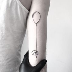 Holding a balloon on the arm tattoo