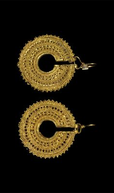 ETRUSCAN GOLD OPENWORK EARRINGS Circa 500 BC. A pair of fabricated gold earrings in opus interrasile comprising a hollow c-shaped body, its inner and outer faces pierced and decorated with filigree beaded wire and granulation;