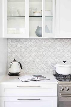 Gorgeous white kitchen boasts carrera marble fan shaped backsplash tiles positioned above white shaker cabinets with long nickel pulls and beneath glass front upper cabinets fixed beside a concealed vent hood mounted above a stainless steel oven range. #Backsplashes #WhiteKitchen #Carrera