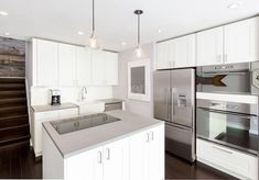 Modern kitchen with white cabinets, dark wood floors and corian solid surface counters