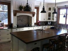 Armoire de cuisine en merisier blanc avec comptoir de granite, hotte décorative et utilitaire. Plusieurs tiroirs dans le bas.
