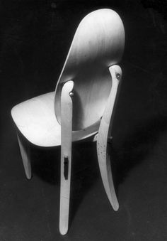 Chair in polished natural wood with curved plywood seat and back: swinging back, nailed joints without the use of glue (Domus 245)