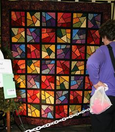 Shattered quilted by Pamela Checketts and Sue's Quilts Shop    Stained Glass quilt from hand batik fabrics. Just look at those colors glow inside the dark sashing.