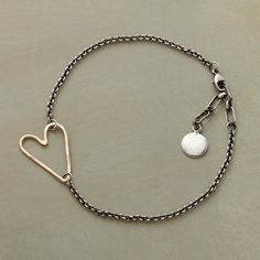 """HEARTLINK BRACELET--A heart hand-formed and hammered of 14kt gold is the loving link within a chain of sterling silver oxidized to black. Lobster clasp. 6-1/2"""" to 7-1/4""""L."""