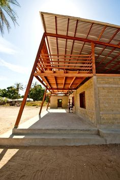 Youth Center In Niafourang by Project Niafourang. Supersized wood truss supports a corrugated metal roof while also containing a balcony space and framing a walkway below.