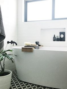 Free standing bath tub with DIY bath tray. Black bathroom tapware, black and white petal tile, black and white bathroom accessories. Bathroom niche styling