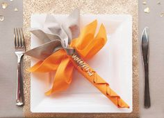 gray and orange napkins are table decorations for thanksgiving and halloween