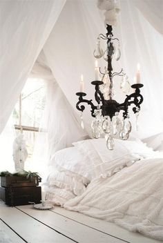 white panted hardwood floors in this casual cottage bedroom.  Love the chandelier!
