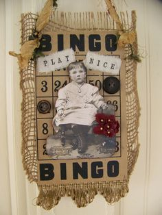 Mixed-media collage art, created with vintage bingo card set on natural burlap, embellished with old image of young girl, tiny dark red flowers, and vintage buttons
