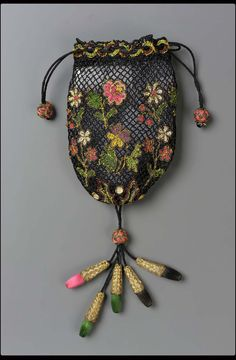 Small oval drawstring bag, black silk net with chain stitch flowers worked with silks and metal thread.