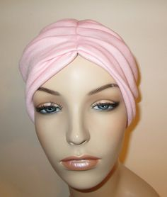 """Pleated Pink Stretch Knit Trendy Hat Chemo Hat Alopecia Head Cover Cancer Hat. Quality handmade in the USA. This hat features pleats both in the front and in the back. It's made of a soft stretchy knit, 95% cotton and 5% lycra. Size: I design my hats to fit heads that measure between 21"""" - 22 1/2"""". If your head is larger or smaller, just let me know. Since these are hand made, we can make them any size you need. This turban comes in White, Black, Navy, Medium Blue, Teal, Gray, Cream…"""