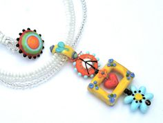 Bella Bead Jewelry- Lampwork Glass Peace, Love and Happiness Necklace. $85.00, via Etsy.