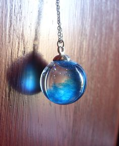 Glass orb necklace with blue feather in resin by zusnA on Etsy
