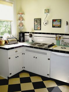 Cute 50's kitchen get's a 30's facelift?  I like the checkerboard on the diagonal. The backsplash tiles remind me of my bathroom tiles. See drawer pull.