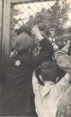 Lodz, Poland, 1942, Children parting from their mothers through a fence.