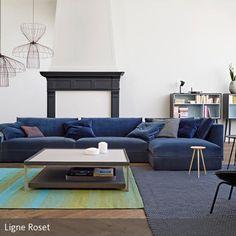 Das große blaue Designer-Sofa bildet den Mittelpunkt dieses vor allem in Blau- und Grautönen gehaltenen Wohnbereichs. Die weißen Wände und der helle …