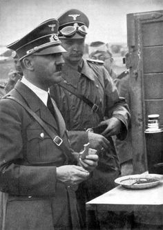 Hitler during the invasion of Poland grabs a quick bite at a field kitchen. A thermos next to his plate most likely contains tea. Hitler wasn't friendly with coffee.