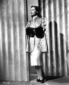 """""""Persian brocade fashions this beautiful coat designed by Yvonne Wood for Ella Raines in The Web.The background of beige is exquisitely patterned in a wheat motif with pure gold embroidery and muted tones of red, blue and green. Wide beaver cuffs set off the sleeves and a matching blue scarf is worn at the neckline."""""""