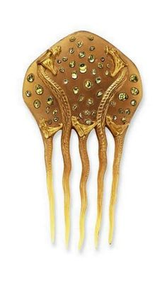 RENÉ LALIQUE   An Art Nouveau horn and peridot hair comb. The shield-shaped carved horn panel depicting two gold stained snakes poised to strike, enhanced by scattered vari-shape cabochon peridots, extending three additional gold stained carved snakes, the tails forming the comb, circa 1898.