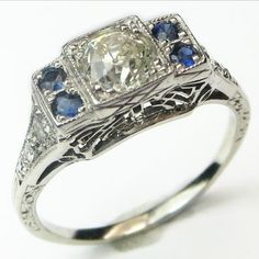 Bluepoint: This pretty panel top ring is punctuated by 4 bright blue, natural sapphire accents framing a scintillating old European cut diamond. Gracefully tapered shoulders drop from the center panel, which is held slightly above the finger on a marvelous bit of stylized Art Deco filigree. Ca.1925. Maloys.com
