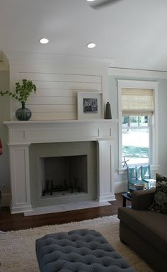 mantel - white wood - grey hearth - clean lines add interest with tufted ottoman