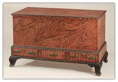 Outstanding Pennsylvania Decorated Blanket Chest attributed to the Leiby School of decoration having a lid and case painted with bold salmon and black swirls, above a stepped base with three drawers with similar vertical feathering and ebonized trim, retaining its original oval brasses, all on tall ogee bracket feet.    Completely original!    Lehigh County, Pennsylvania, circa 1815.