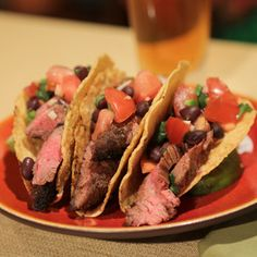 Meanwhile, combine the black beans, cilantro, lime juice, oil, tomatoes, garlic, jalapeno and the remaining 1/4 teaspoon salt in a large bowl and toss to coat well. Evenly divide the steak slices among the tacos. Top each taco evenly with black bean pico de gallo.