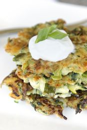 Zucchini Fritters from Our Best Bites 4  cups grated zucchini 1/2 teaspoon salt 1/4 cup shredded Parmesan cheese 1/4 cup sliced green onions 1/8 teaspoon black pepper 1/2 teaspoon bottled minced garlic 2 tablespoons all purpose flour 1 egg white (reserve the yolk) olive oil (I recommend our Garlic Olive Oil)
