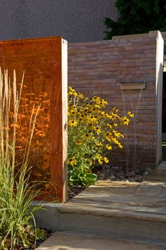 Four screens of various dimensions emerge from the planting and help to obscure the rear of the space from view.  Each screen features a different material: wooden panelling, textured stone tiles, stainless steel mesh and orange Perspex.   #tiles #gardenwall #perspex #rudbeckia
