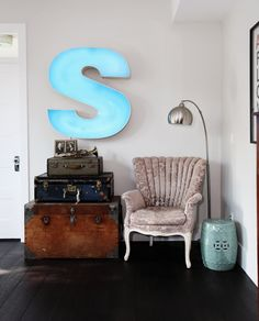 Vintage suitcases, industrial letter, and a beautiful upholstered chair