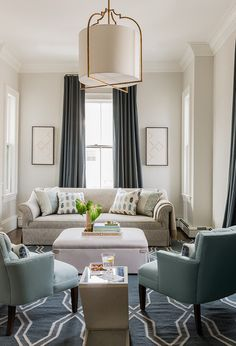 Symmetry can make a small space feel important. Sneaking in symmetry where you can is a great way to bring a bit of grandeur to a compact space. Here a set of floor-sweeping drapes and a pair of artworks frame the window, while a pair of matching armchairs and matching pillows bring a pleasing sense of order to the seating area.