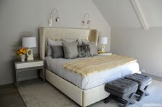 Beautiful bedroom features an cream velvet bed with wingback headboard dressed in gray bed linens, charcoal gray pillows, platinum gray pillows and a cream faux fur throw illuminated by a pair of Regina Andrew Arc Wall Sconces.