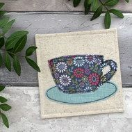 A fabric cup coaster in a beautiful combination floral print & plain blue fabrics, a quirky and unique housewarming gift idea, especially for anyone who loves a cuppa! The coaster has a tea cup & saucer appliquéd in 100% cotton fabric using a f...