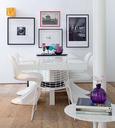 Molduras pretas em fotos pb não dão margem para erros. É por isso que o designer de interiores Francisco Calio deu um toque de esperteza à sua sala com o acréscimo de uma moldura vermelha fininha. O resto da sala de jantar é todo branco