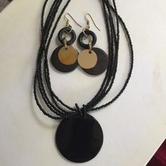 Black need set 5 Rows of black beads held together with a lobster claw .  In the middle a large black circle.it also has matching pierced earrings with gold tone circles n smaller black open disc n a larger disc in the back.  Great look, great buy !!!!! Jewelry Necklaces