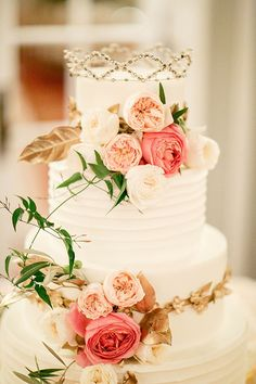 A white wedding cake with fresh flowers topped with the bride's grandmother's wedding crown | Brides.com