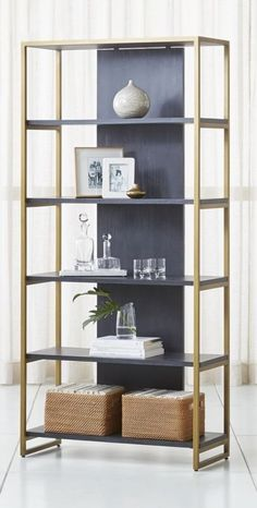 Wire-brushed and black-stained acacia wood provides the shelves and back panel for the bookcase's iron frame finished in antique bronze.  The Oxford Wide Black Wood Bookcase is a Crate and Barrel exclusive.